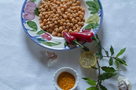 garbanzos: garbanzos en un recipiente con la c�rcuma, chiles rojos, lim�n y ajo, en un mantel blanco,