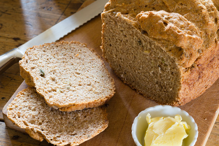 home baked: home baked wholemeal bread on a wooden board with a dish of butter.