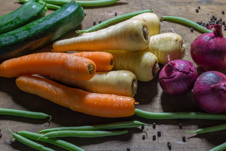 parsnips: vegetables, carrots, parsnips, onions, green beans and courgettes, grouped together on a wooden table.