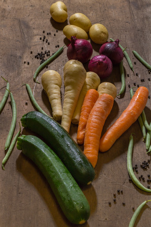 parsnips: vegetables, carrots, parsnips, onions, green beans and courgettes, grouped together as produce on a wooden table.