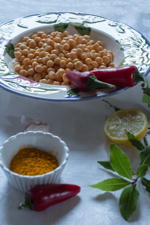 garbanzos: garbanzos en un recipiente con la cúrcuma, chiles rojos, limón y ajo, en un mantel blanco,