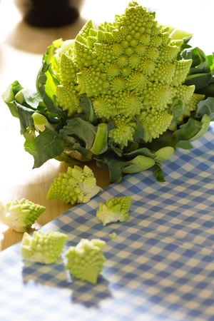 romanesco broccoli or cauliflower with florets scattered on a pale wood background and gingham cloth.