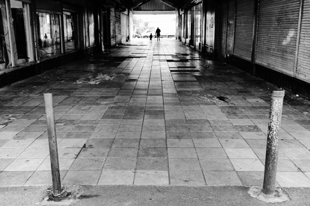 urban decay: light at the end of the walk way or tunnel, containing empty shops and urban decay and people Stock Photo