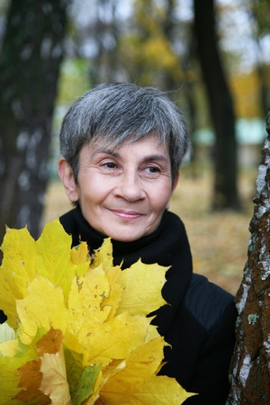 Senior smiling woman holding autumn leaves Stock Photo