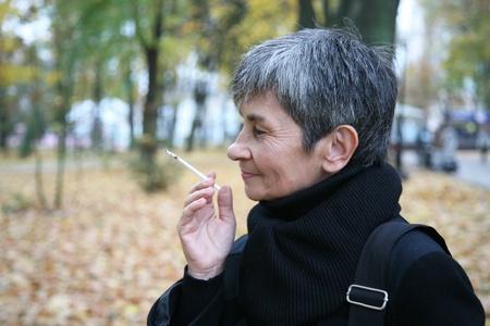 Senior woman smoking a cigarette in the street Stock Photo