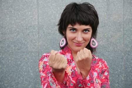 Smiling young woman holding fists photo