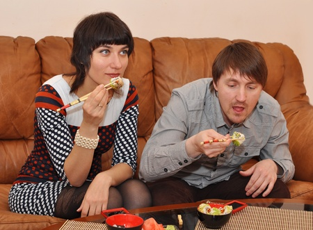 diningroom: Married couple eating sushi in the dining-room Stock Photo