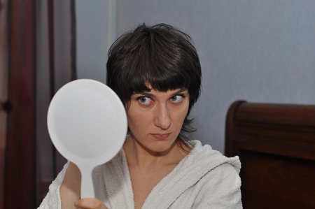 Young woman looking in the white hand mirror