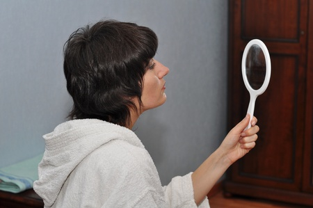 Young woman looking in the white hand mirror Stock Photo - 13556313