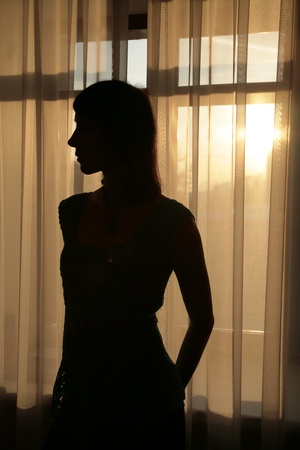 Silhouette of young woman against curtains Stock Photo