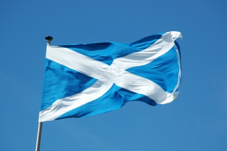 Waving in the blue sky flag of Scotland Stock Photo