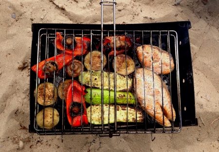 Grilled vegetables mushrooms and fish on the sand