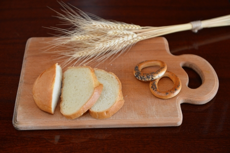 Still life with wheat ears, white bread and bagels on the light wooden board