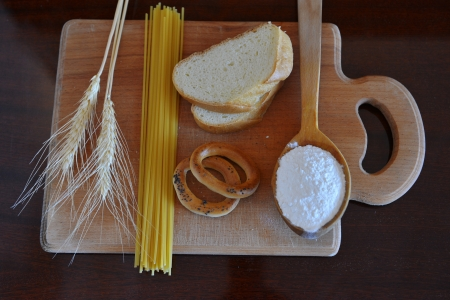 Light wooden board with wheat ears and presented food which can be made of white flour Stock Photo