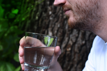 Close-up of male chin and hand with glass of water