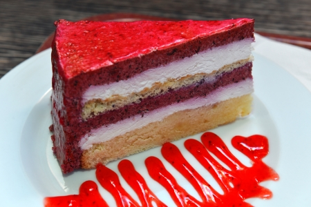 A piece of tasty cake made of berries with jam on the plate