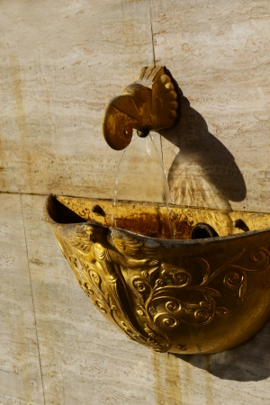 Close-up of the golden fountain with the flowing water