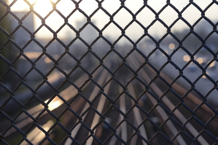 Rails and city visible through metal grid