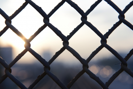 Close up of metal grid against city background