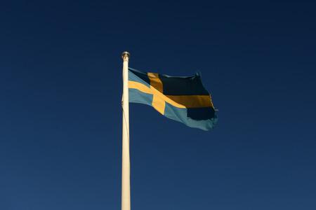 Swedish flag waving against blue sky Stock Photo