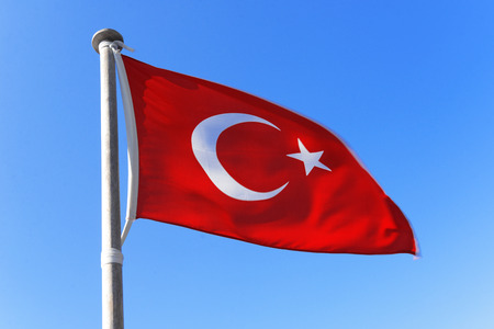 Flag of Turkey waving against blue sky