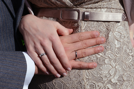 Hands of just married couple overlaying belly of the pregnant bride photo