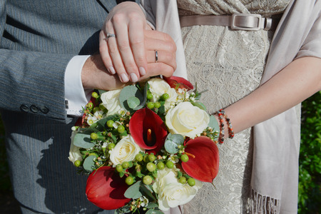 Hands of just married couple holding bunch of flowers photo