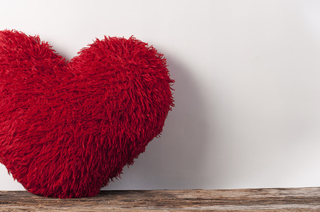 love shape: Fluffy soft red heart. Pillow on wood board. Stock Photo