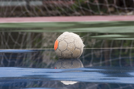 An old soccer ball on wet field, goal is the background Stock Photo