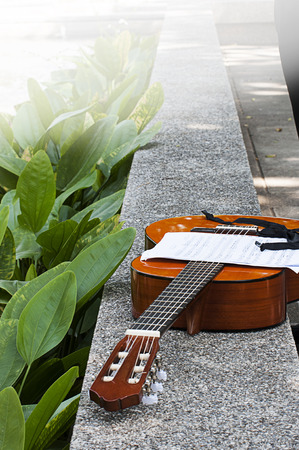 classical guitar and note sheet in the park