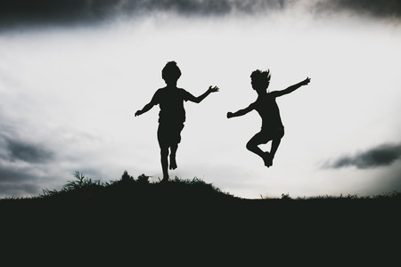 Silhouettes of kids jumping from a sand cliff at the beach photo