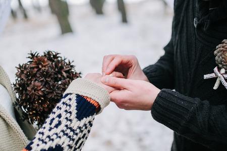 Groom putting wedding ring on brides finger photo