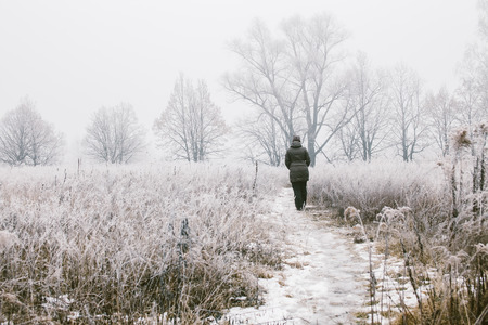 Woman walking in the field on a foggy winter day photo