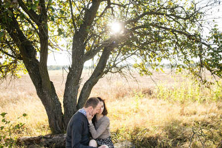 Image of a young couple hugging while sitting under a tree at autumn sunset photo
