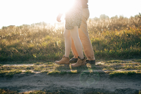Image of a young couple that walks holding hands at autumn sunset photo