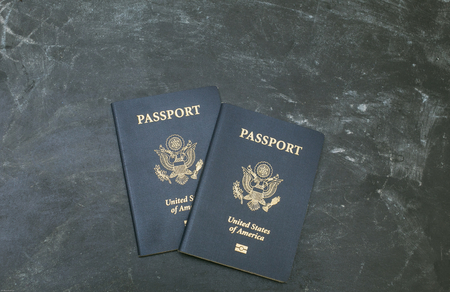 citizenship: Two US passports on black background. American citizenship. Traveling around the world.