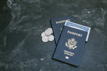 Two American passports on black background. American citizenship. Social security card in a document. Traveling around the world. Coins on a side photo