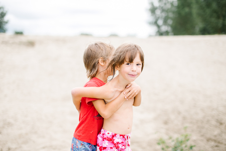 fraternal: Cute smiling fraternal twins enjoying their time at the beach. Brother and sister hugging. Having fun during summer vacation. Family time at the beach Stock Photo