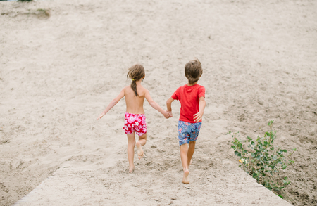 fraternal: Fraternal twins run barefoot holding hands at the beach. Active healthy kids enjoying their time at the beach. Brother and sister playing together. Friends having fun during summer vacation. Nice day at the lake.