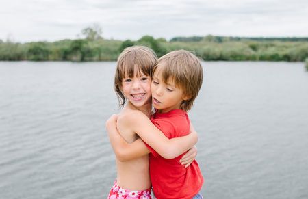 fraternal: Cute smiling fraternal twins enjoying their time at the beach. Brother and sister hugging. Friends having fun during summer vacation. Nice hot day at the lake. Stock Photo