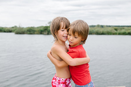 fraternal: Cute happy fraternal twins enjoying their time at the beach. Brother and sister hugging. Friends having fun at summertime. Nice day with family at the lake