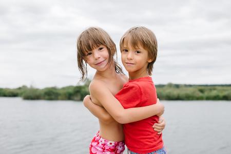 brothers playing: Lindos gemelos fraternos felices disfrutando de su tiempo en la playa. Hermano y hermana abrazos. Divertirse durante las vacaciones de verano. Hermoso d�a con la familia en el lago Foto de archivo