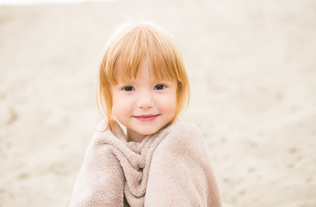 Portrait of a cute toddler girl with red hair wrapped in a towel at the beach smiling at camera. Little girl sitting on sand. Family time at the beach on hot summer day. photo