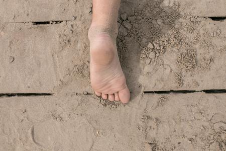 ni�os caminando: Ni�o peque�o pie desnudo en la cubierta de madera en la playa en un d�a caluroso de verano. Divertirse en verano.