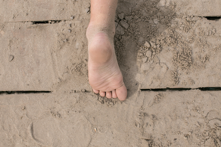 Toddler bare foot on wooden deck at the beach on hot summer day. Having fun at summertime.