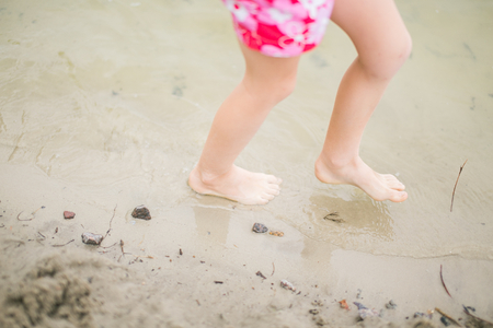 bodypart: Toddler feet in water at the beach. Child in pink shorts walking barefoot in transparent lake water. Having fun at summertime.
