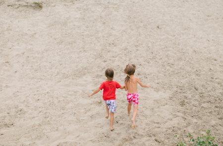 fraternal: Fraternal twins running barefoot at the beach.