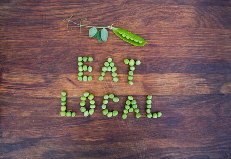 pea pod: Sign Eat Local made of green peas and pea pod with leaves on wooden background. Organic vegetable produce at a farm.