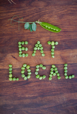 pea pod: Phrase Eat Local made of green peas and pea pod with leaves on wooden background. Organic vegetable produce at a local farm.