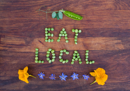 pea pod: Sign Eat Local made of green peas and pea pod with leaves on wooden background. Edible flowers in the bottom. Organic vegetable produce at a farm. Stock Photo